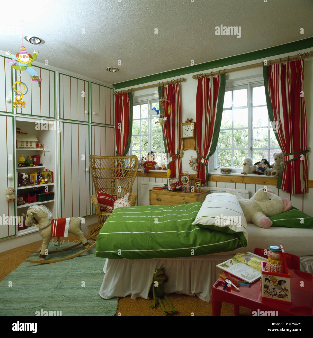 White Walls With Green Detail In Eighties Children S Bedroom With Green Duvet And Red Drapes Stock Photo Alamy