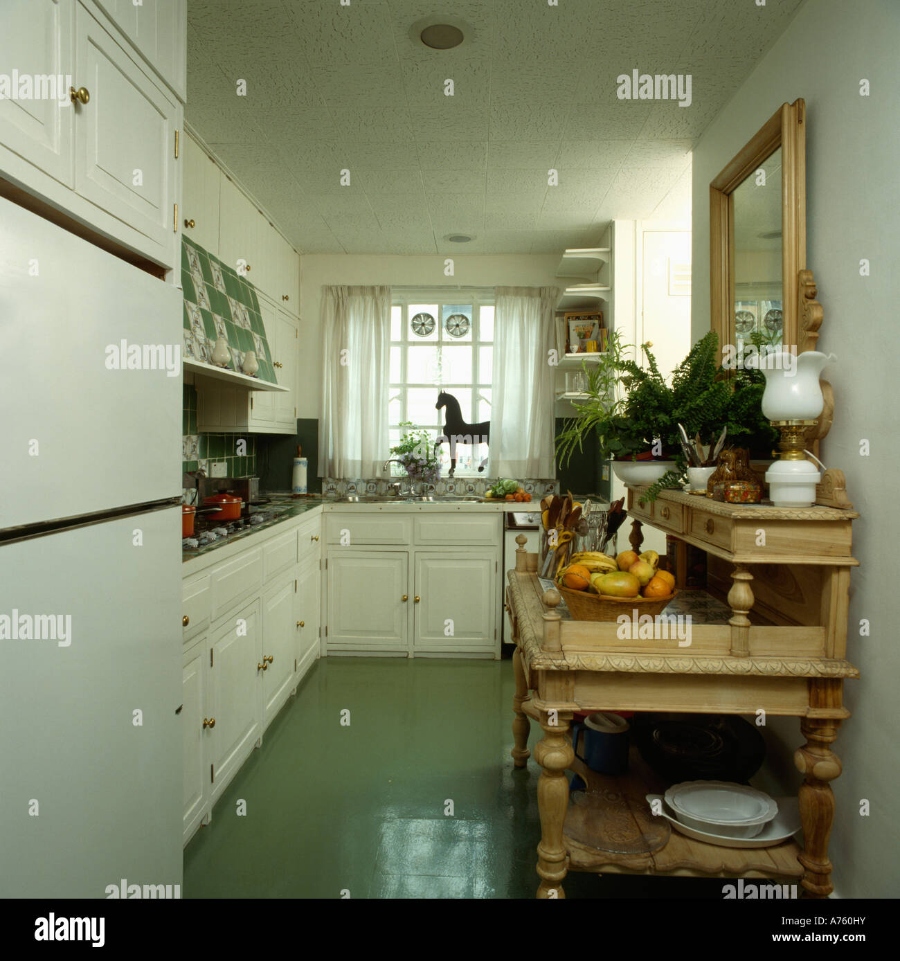 Green Floor In Narrow White Kitchen With Small Pine