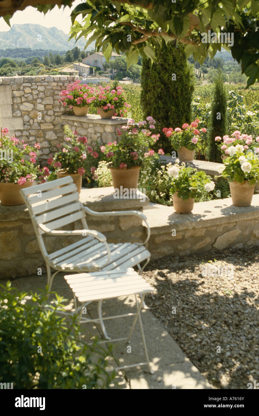 Shady gravel terrace with white garden chair and row of pink Stock ...