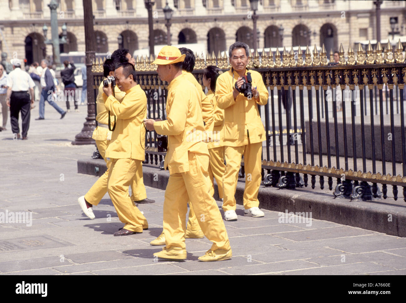 Tourists assumed dressed in yellow as members of visiting sports team sightseeing in French Place De La Concorde Paris street scene France - Stock Image