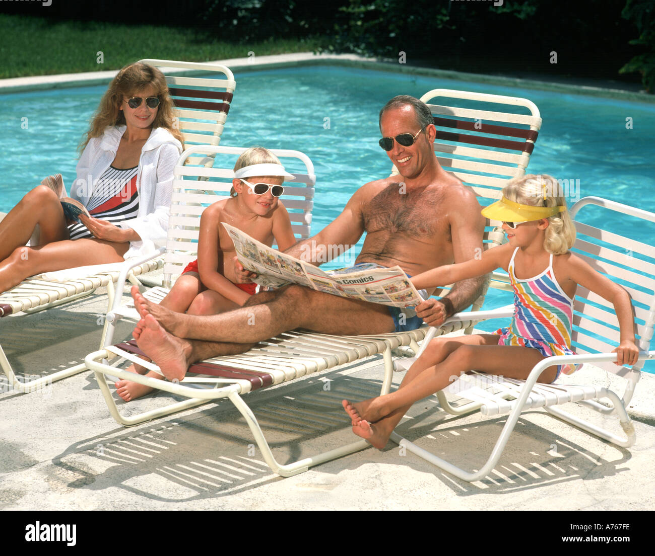 family of four relaxing by pool reading comics - Stock Image