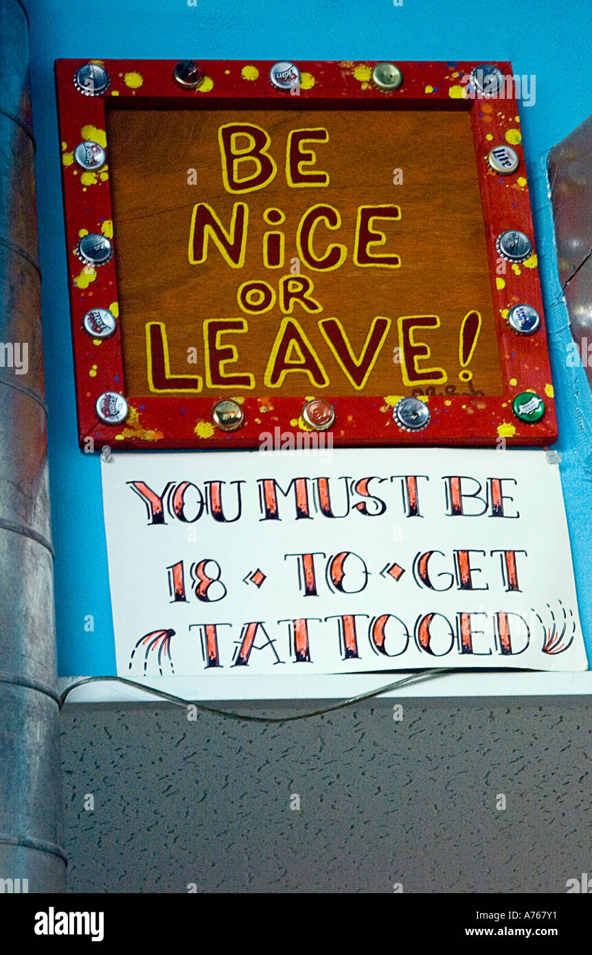 Sign in tattoo parlor which reads 'be nice or leave.' - Stock Image