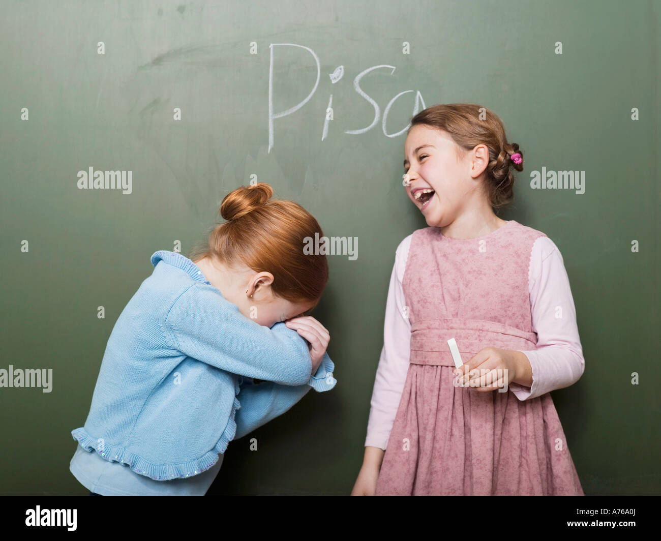 Girls (4-7) standing in front of blackboard, laughing - Stock Image