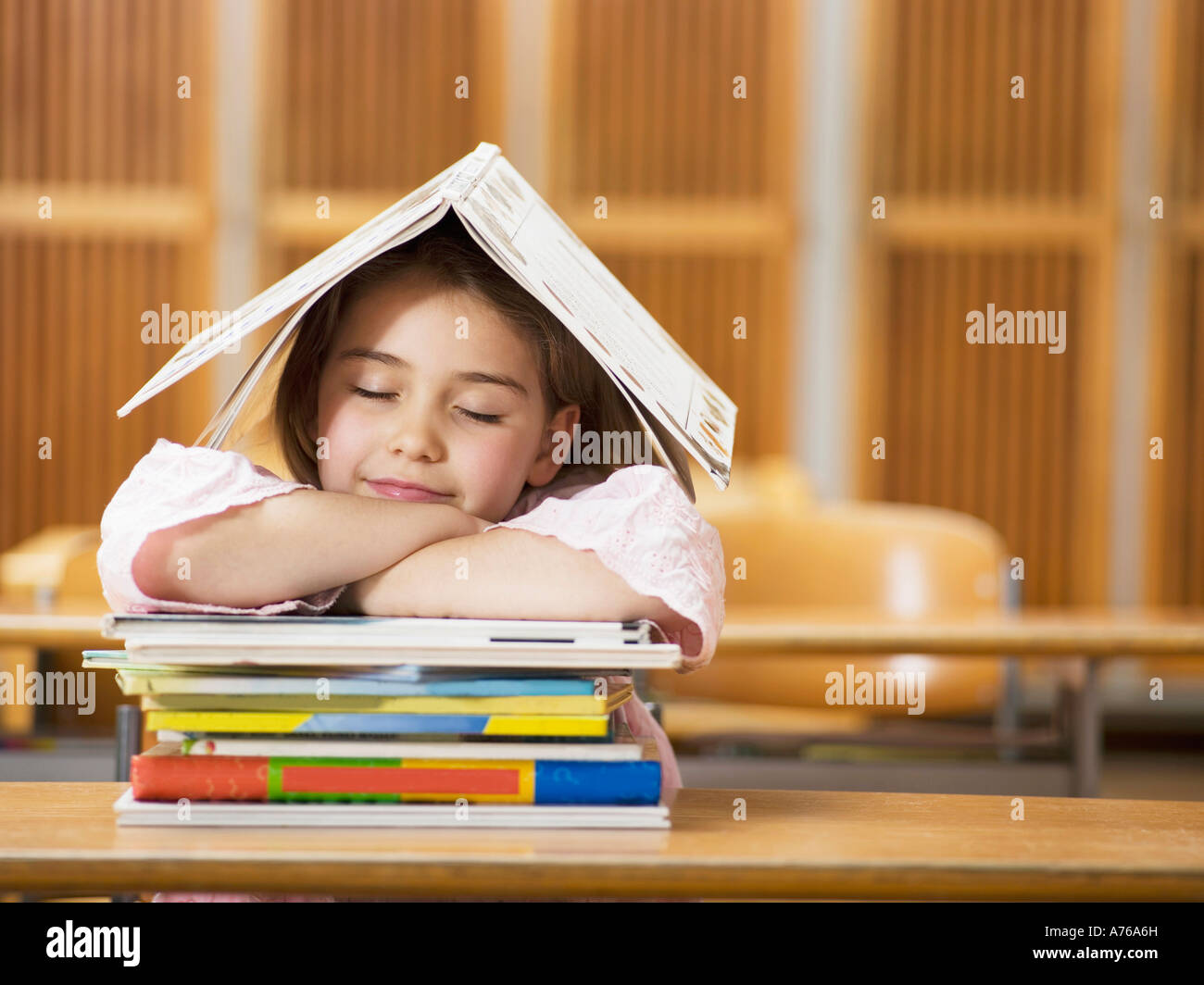 Girl (4-7) sitting desk, leaning on stack of books, eyes closed - Stock Image