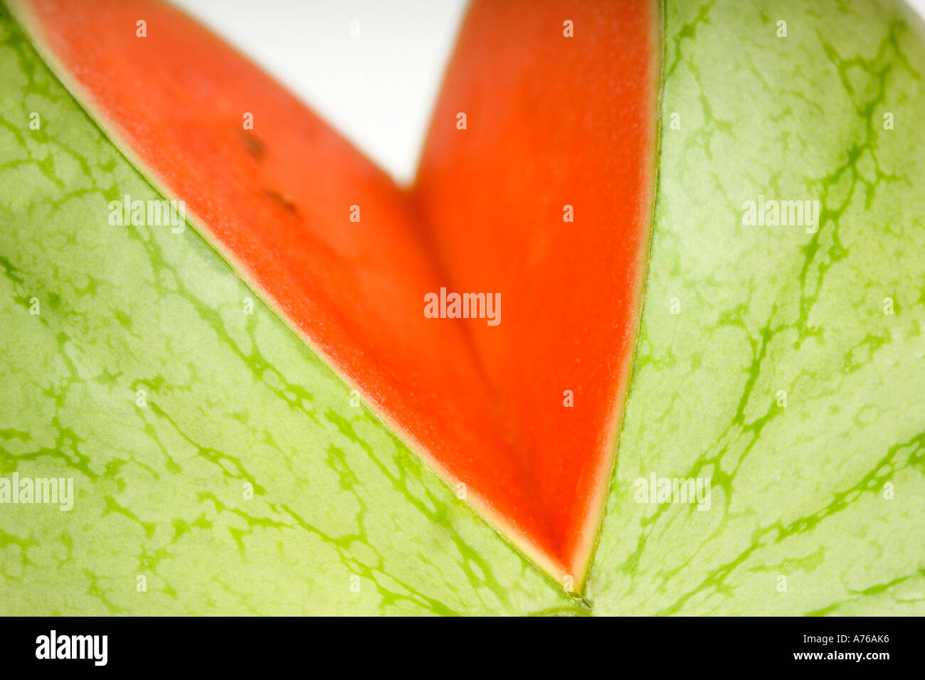Close up of a whole watermelon with a slice cut out on a pure white background. - Stock Image