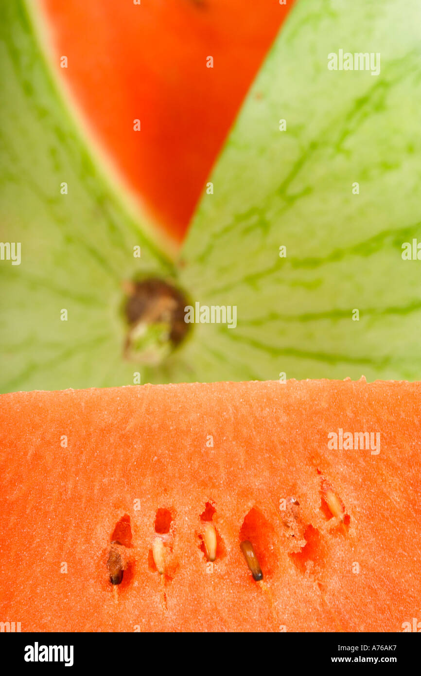 Close up of a whole watermelon with a slice cut out. - Stock Image