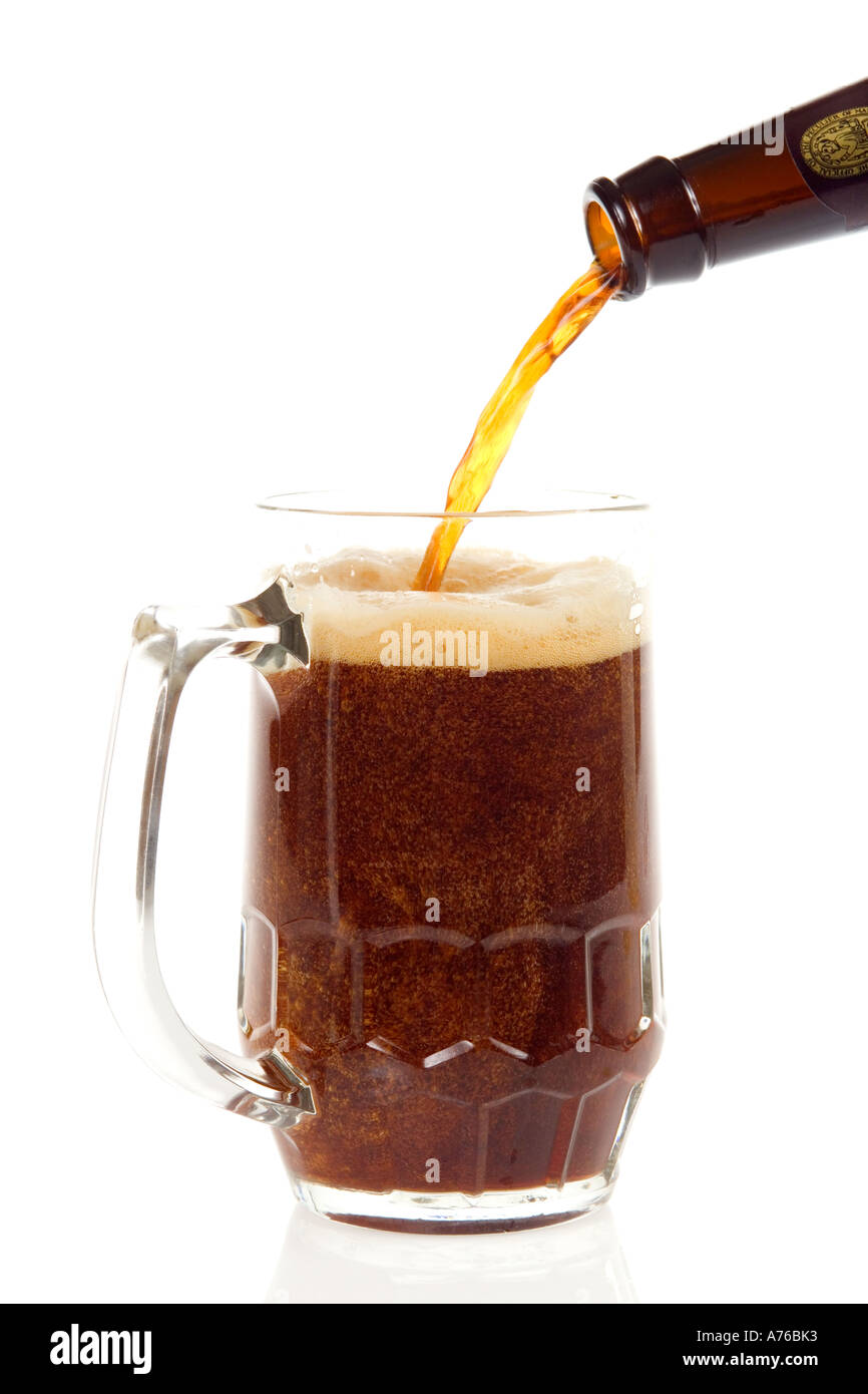 Pint of dark beer being poured into glass on a pure white background. - Stock Image