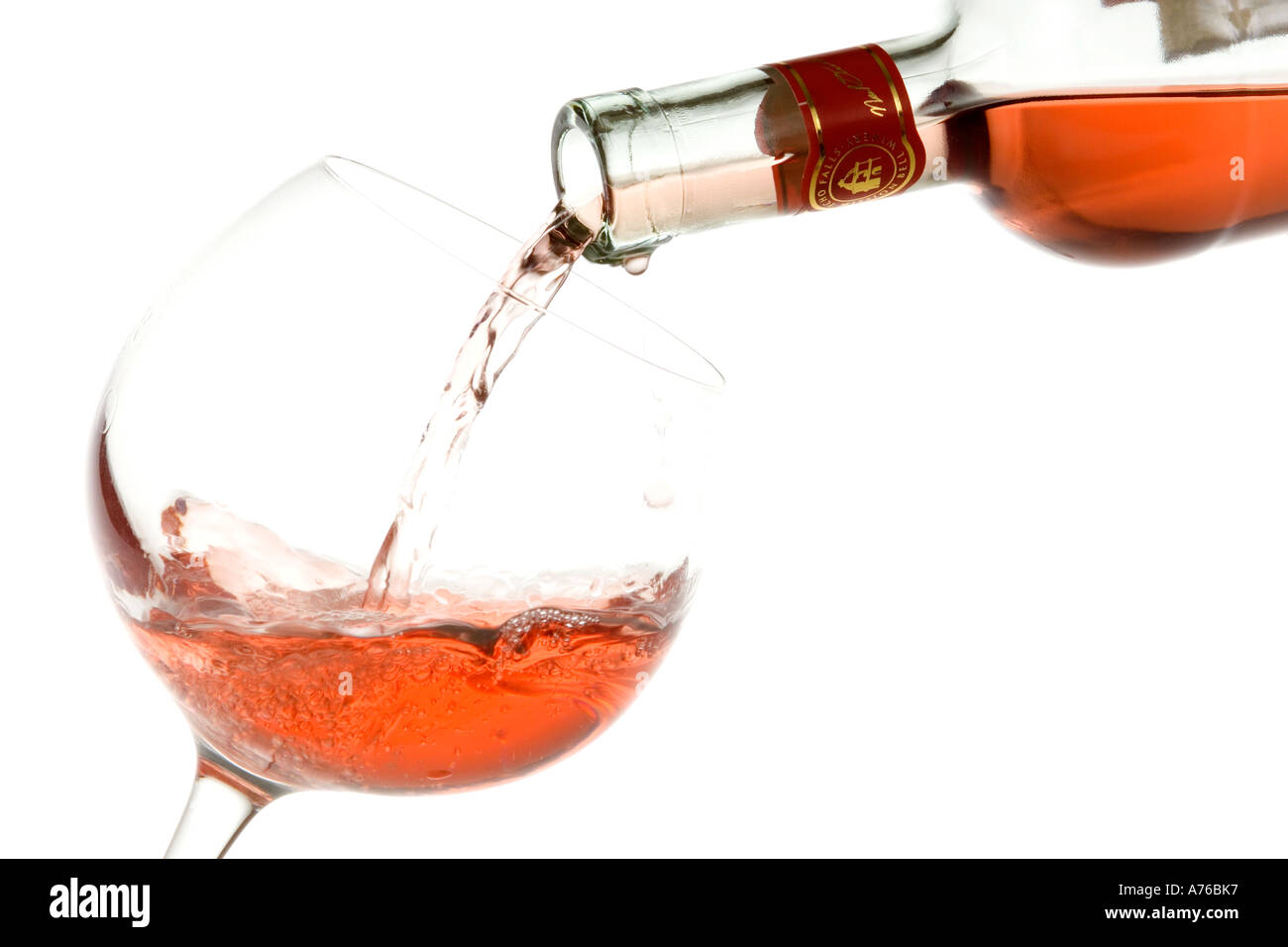 Rose wine being poured into a large glass on a pure white background Stock Photo - Alamy