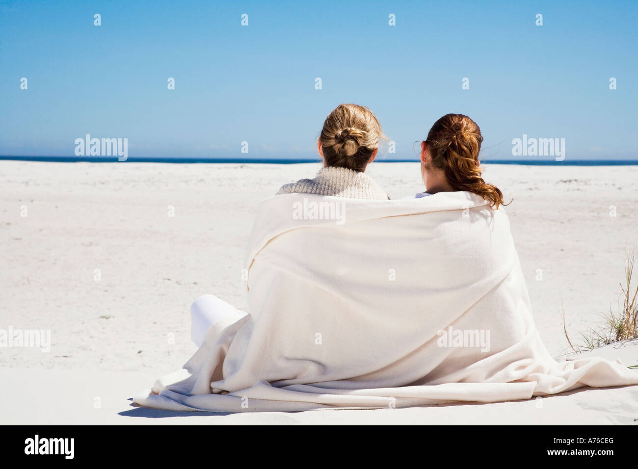 Mother and daughter sitting on beach, rear view - Stock Image