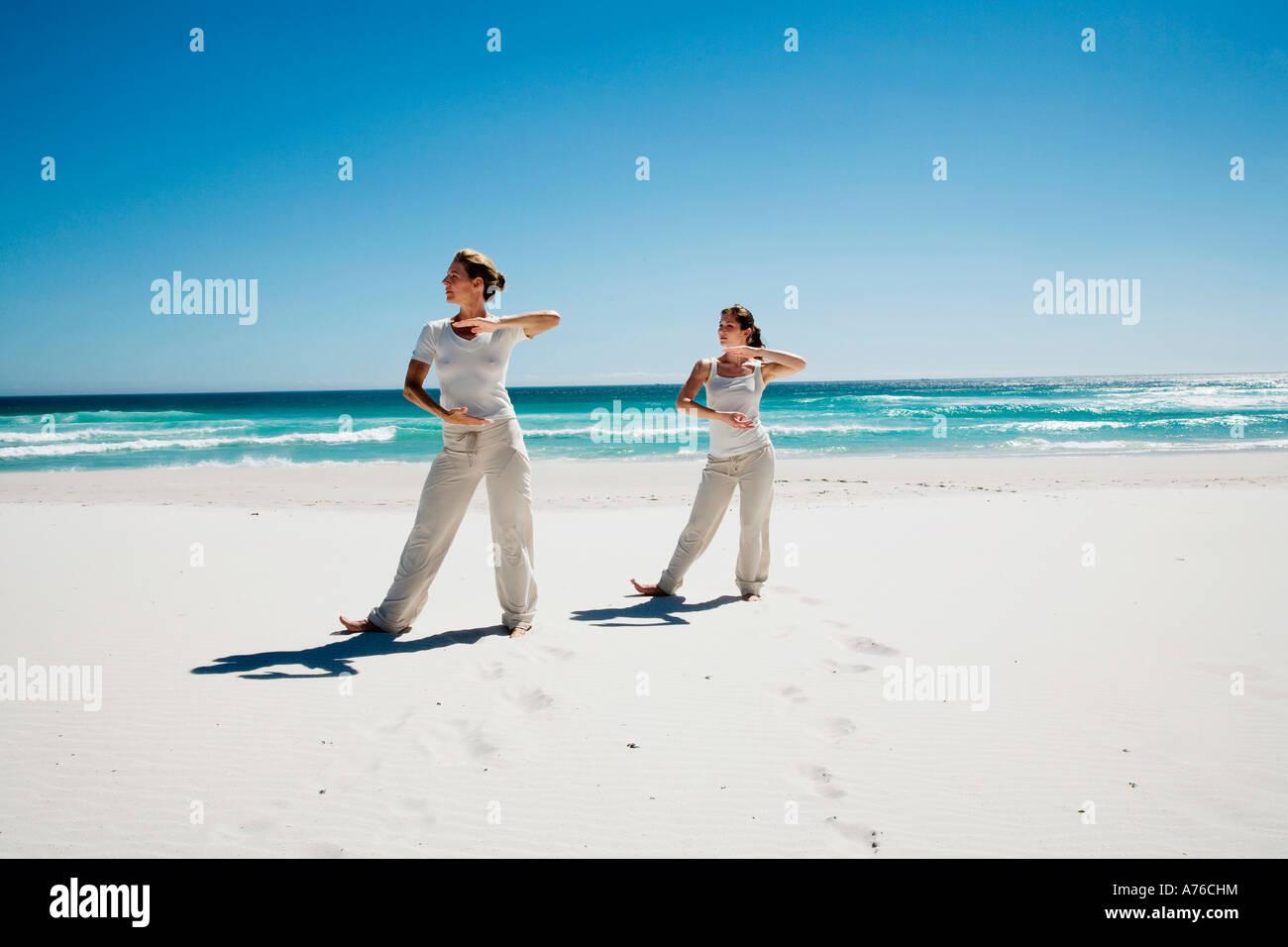 Two women exercising yoga on beach - Stock Image