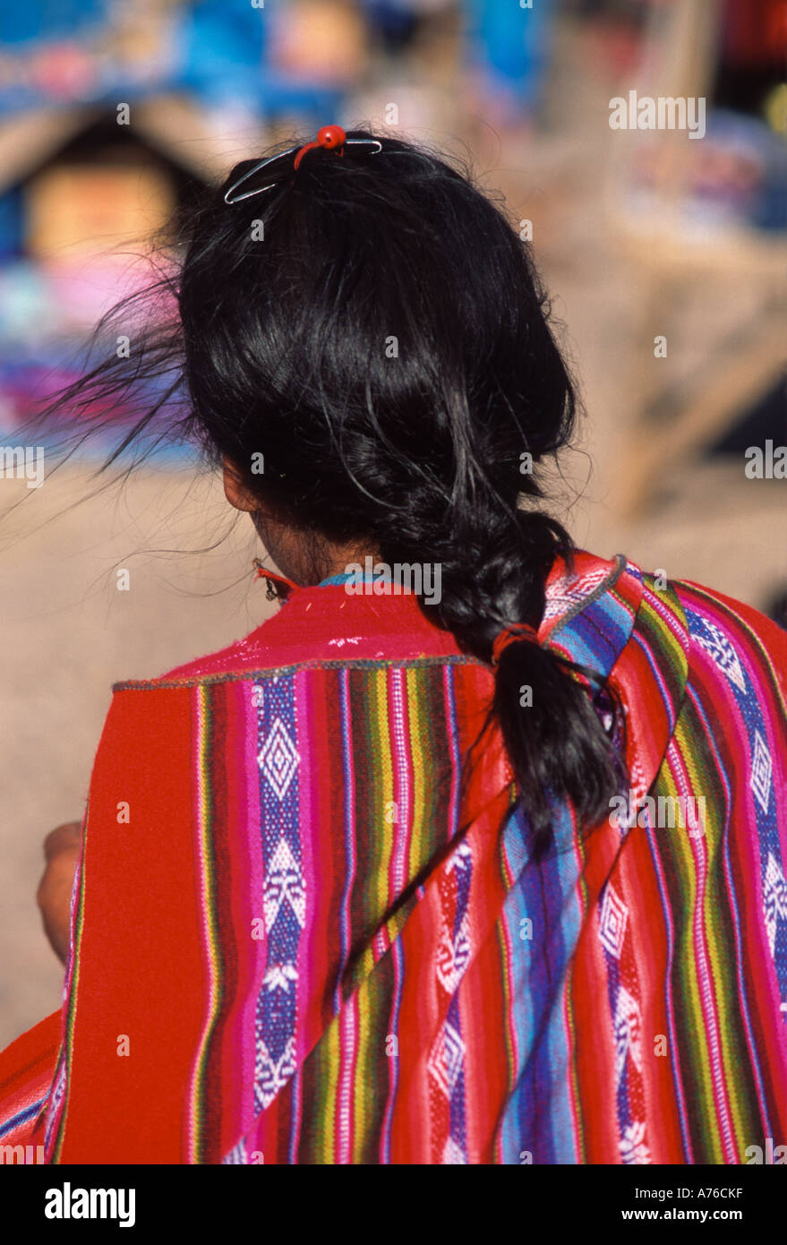 Young Quechuan woman girl with braided hair and colourful traditional clothes , near Cusco , Peru - Stock Image