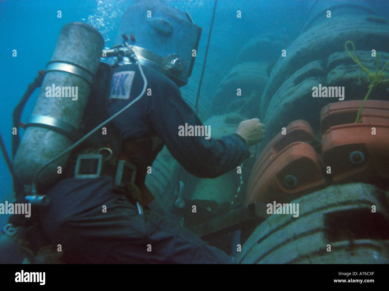 A commercial diver working on an SBM pipe line having just changed one of the flotation devices. Stock Photo