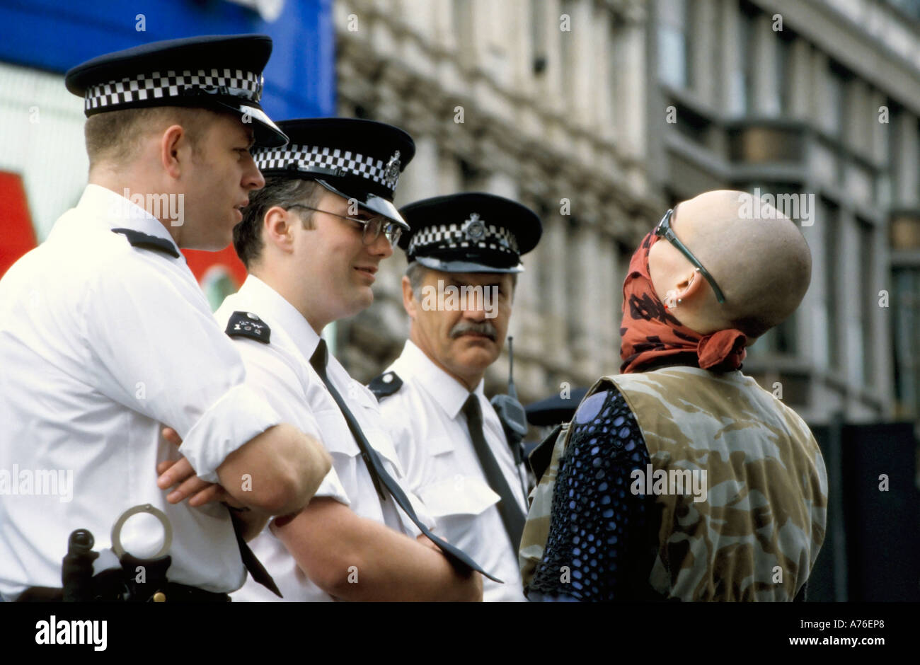 Three policemen talking to a skinhead demonstrator during the May Day demonstrations. - Stock Image