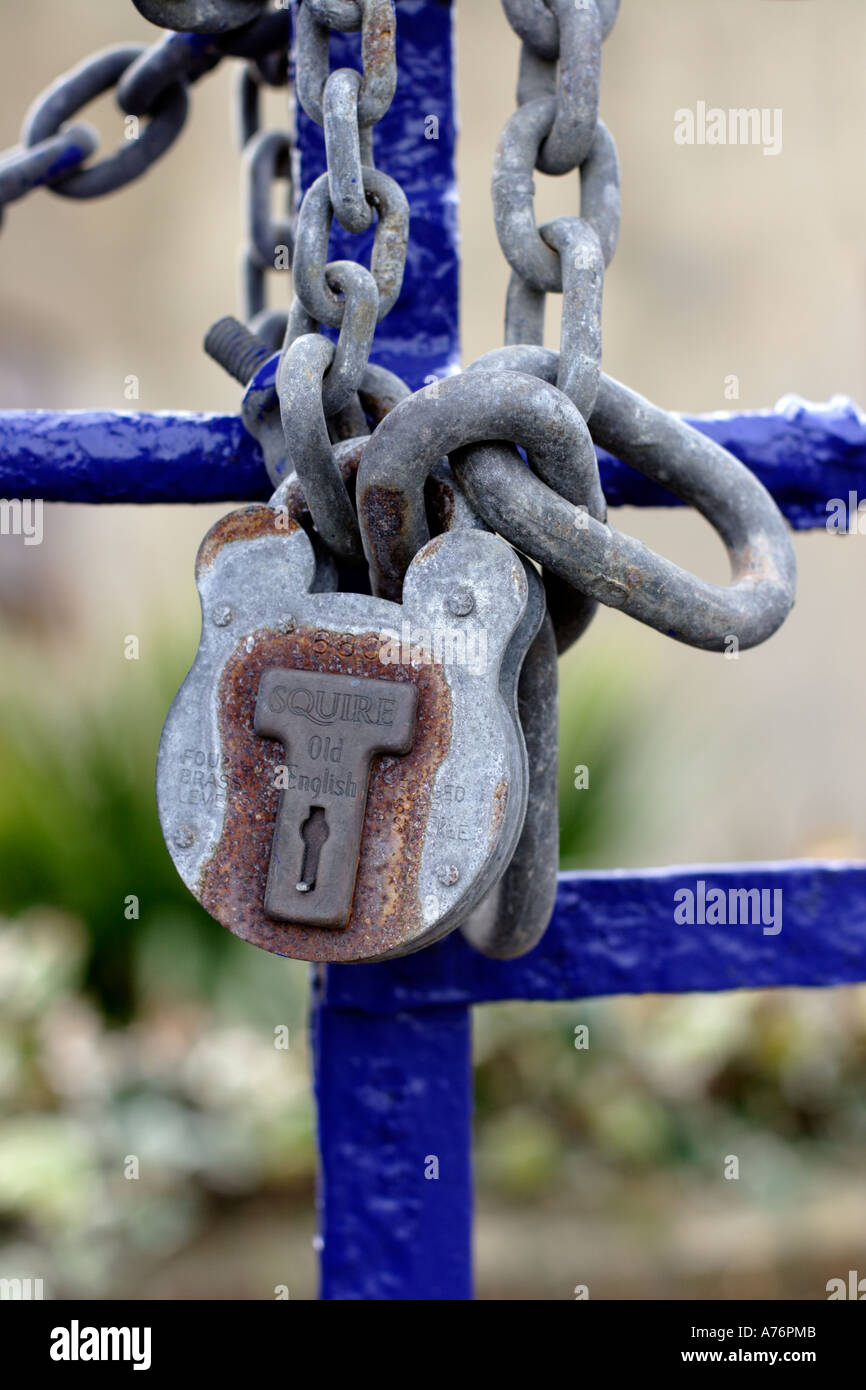 Rusty galvanised steel padlock and chain on blue painted metal fence - Stock Image