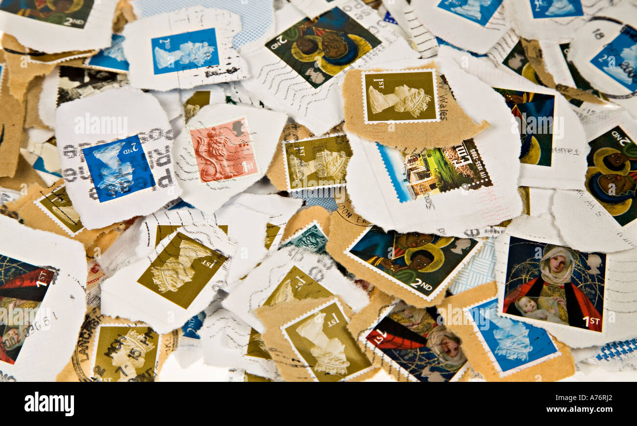 Pile of used franked British postage stamps torn from envelopes for collection - Stock Image