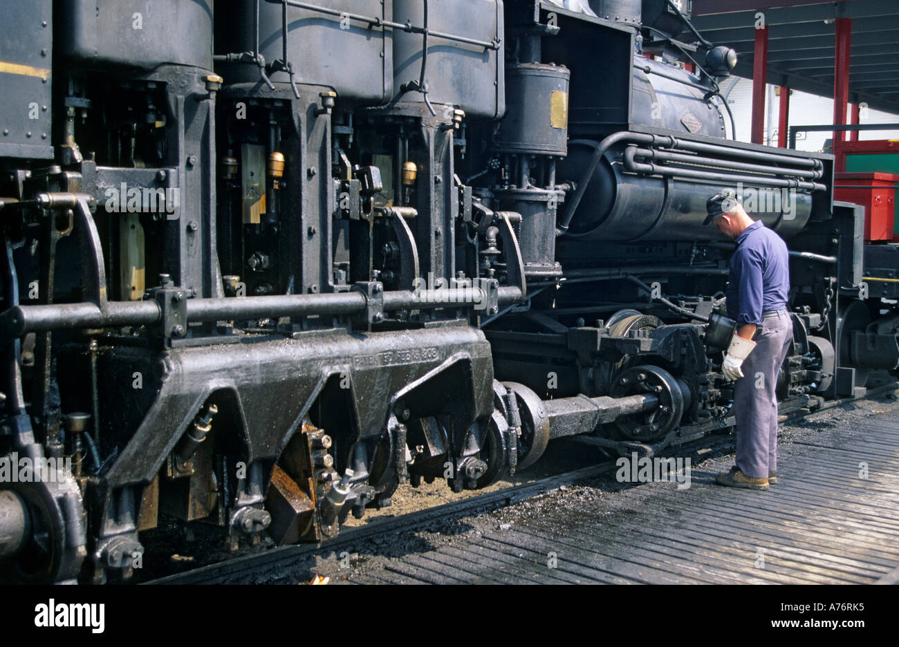 Engineer oiling bearings on steam locomotive Cass Scenic Railroad state park West Virginia USA - Stock Image