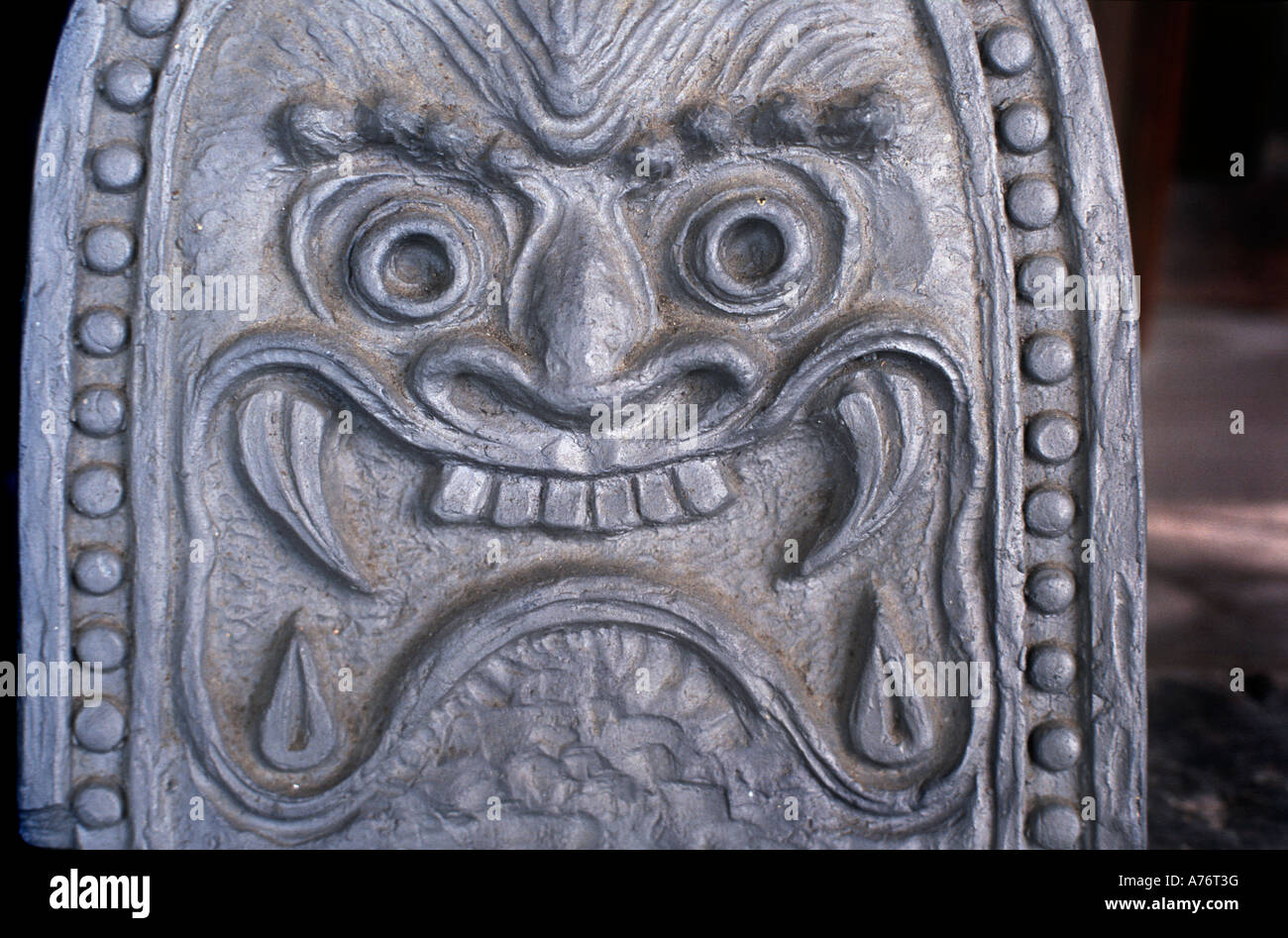 Sculpted roof tile at eaves Face with fierce features Japan - Stock Image