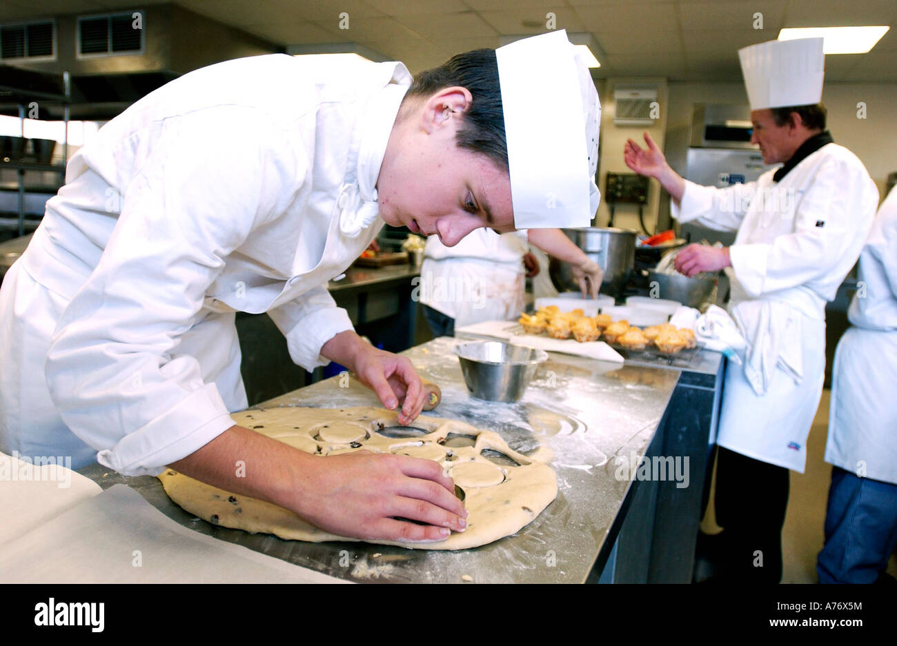 Young man studying catering makes pastry in a class in a modern kitchen - Stock Image