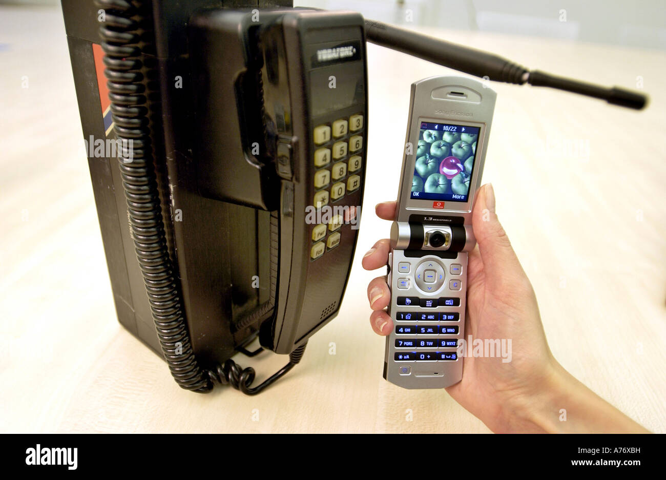 The history of mobile phones displayed with an old model from the 1980s and a 3G Vodafone. - Stock Image