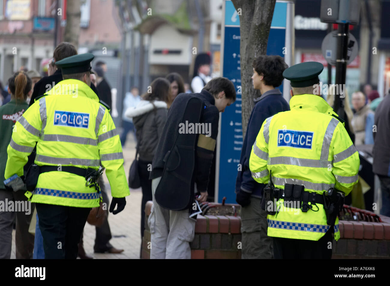 two PSNI police officers on patrol in pedestrian area of belfast in day glo luminous hi vis jackets during christmas shopping - Stock Image