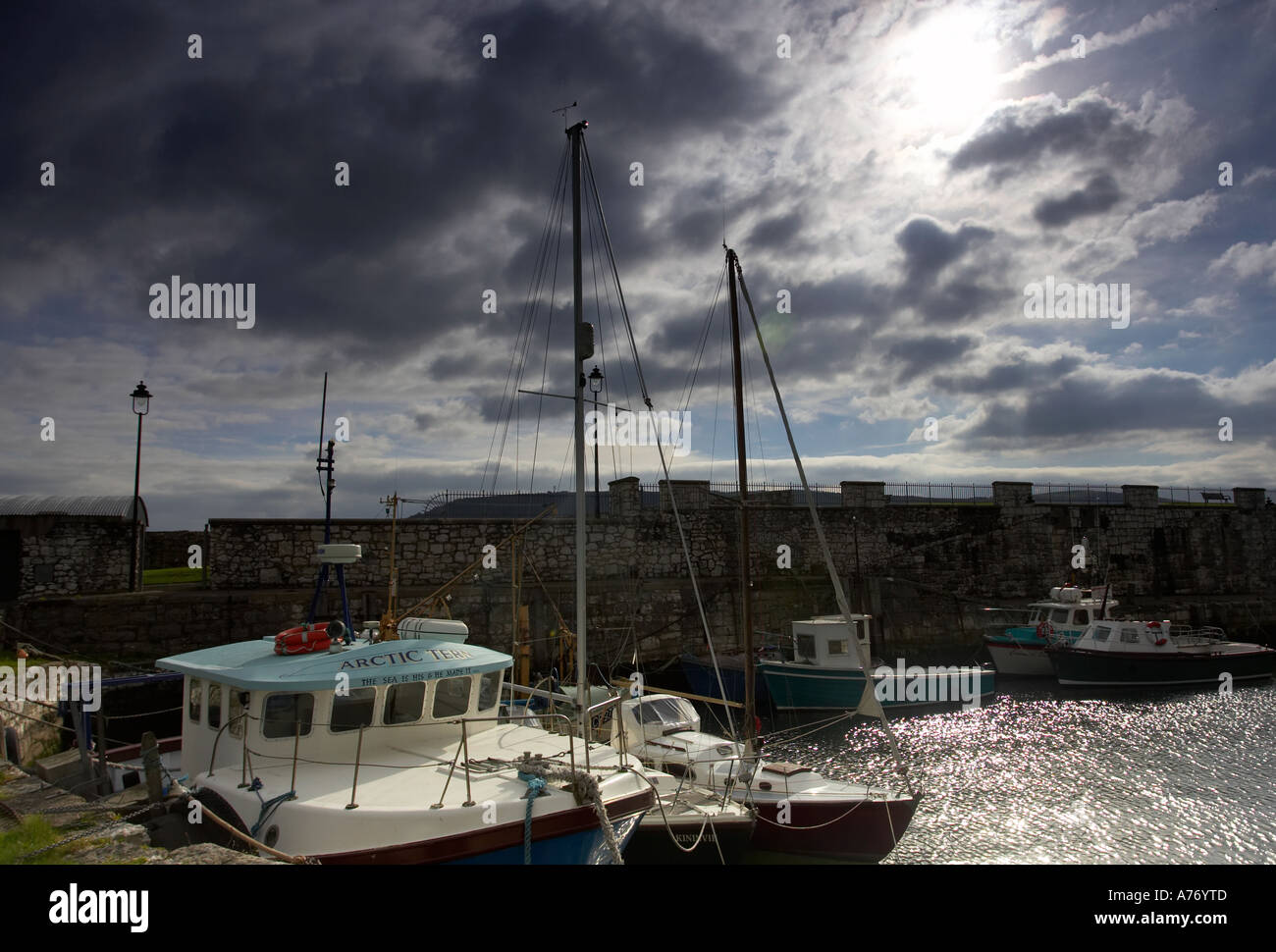 fishing boats tied up in the harbour under stormy skies Carnlough Village county Antrim Northern Ireland - Stock Image