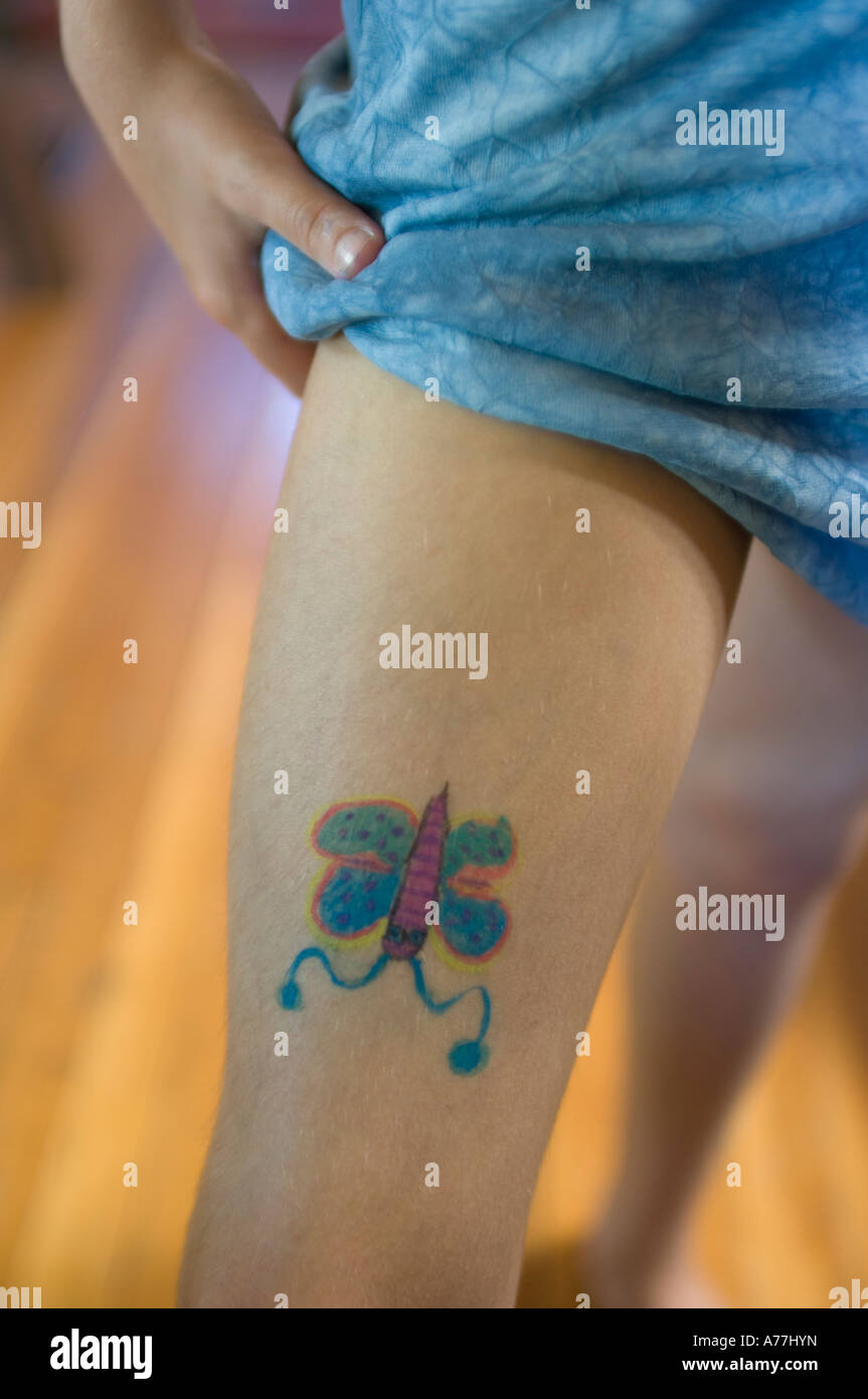 Young girl showing off self inflicted butterfly painting on leg as a non permanent tattoo - Stock Image
