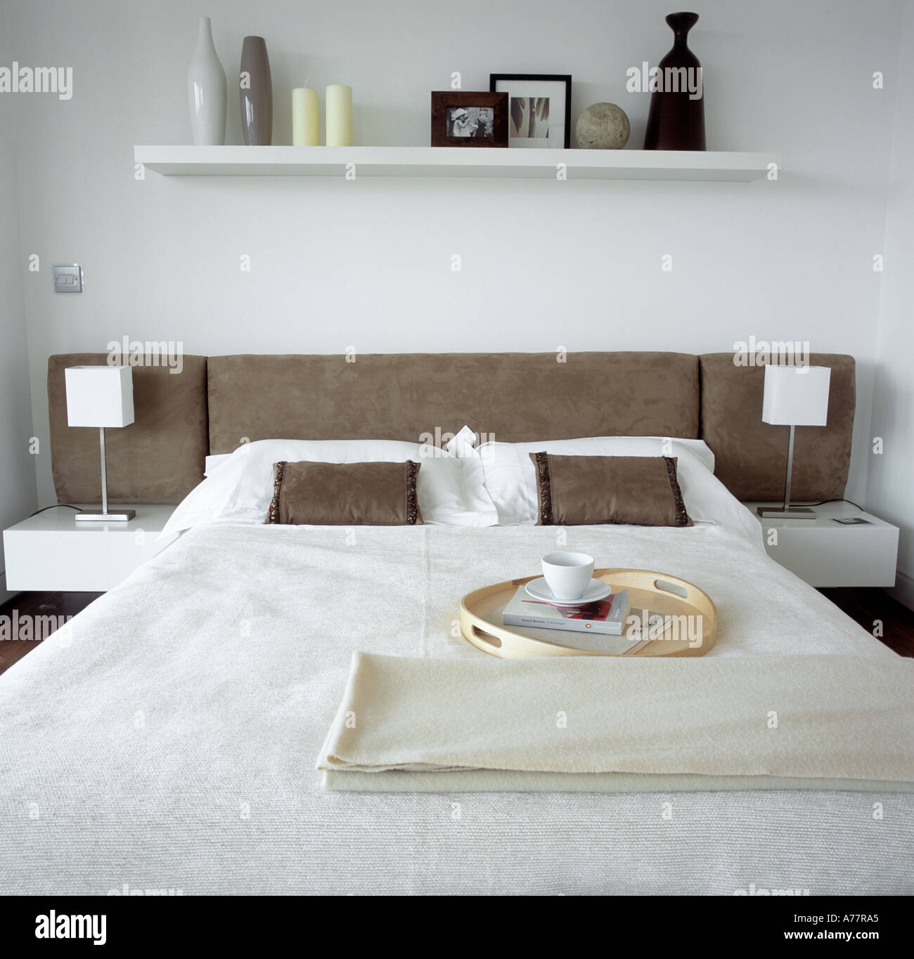 Contemporary bed with cream cover and shelf above bed