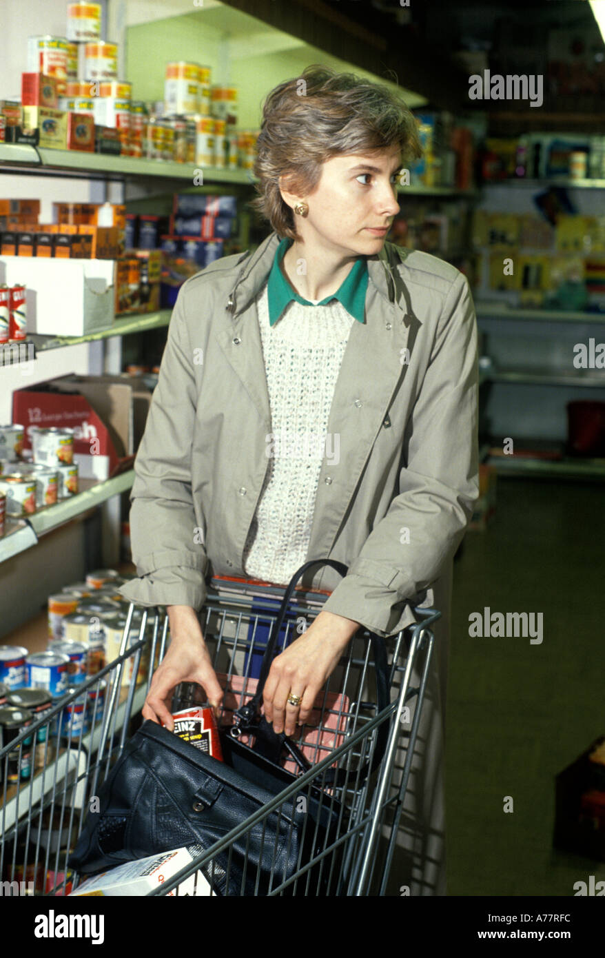 woman shop lifting in supermarket - Stock Image