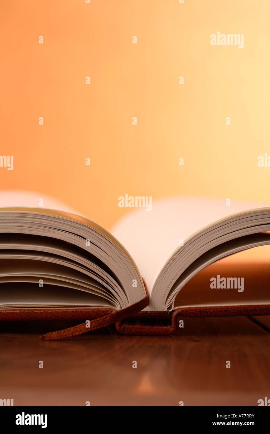 Open leather bound book with warm background - Stock Image
