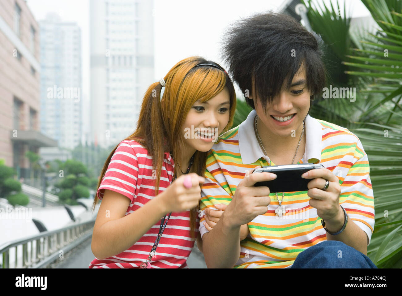 Teenage couple playing with handheld video game, outdoors Stock Photo
