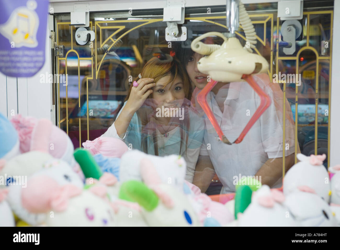 Teenage couple looking at toy grabbing game in video arcade - Stock Image
