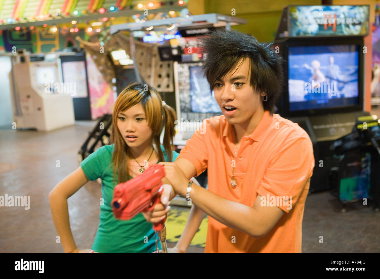 Teenage couple playing game in video arcade - Stock Image
