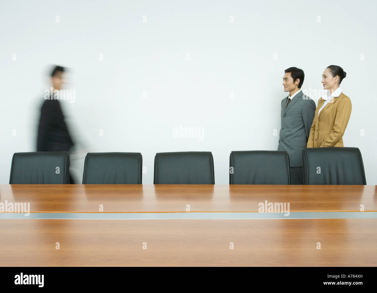 Two business partners greeting associate in conference room - Stock Image