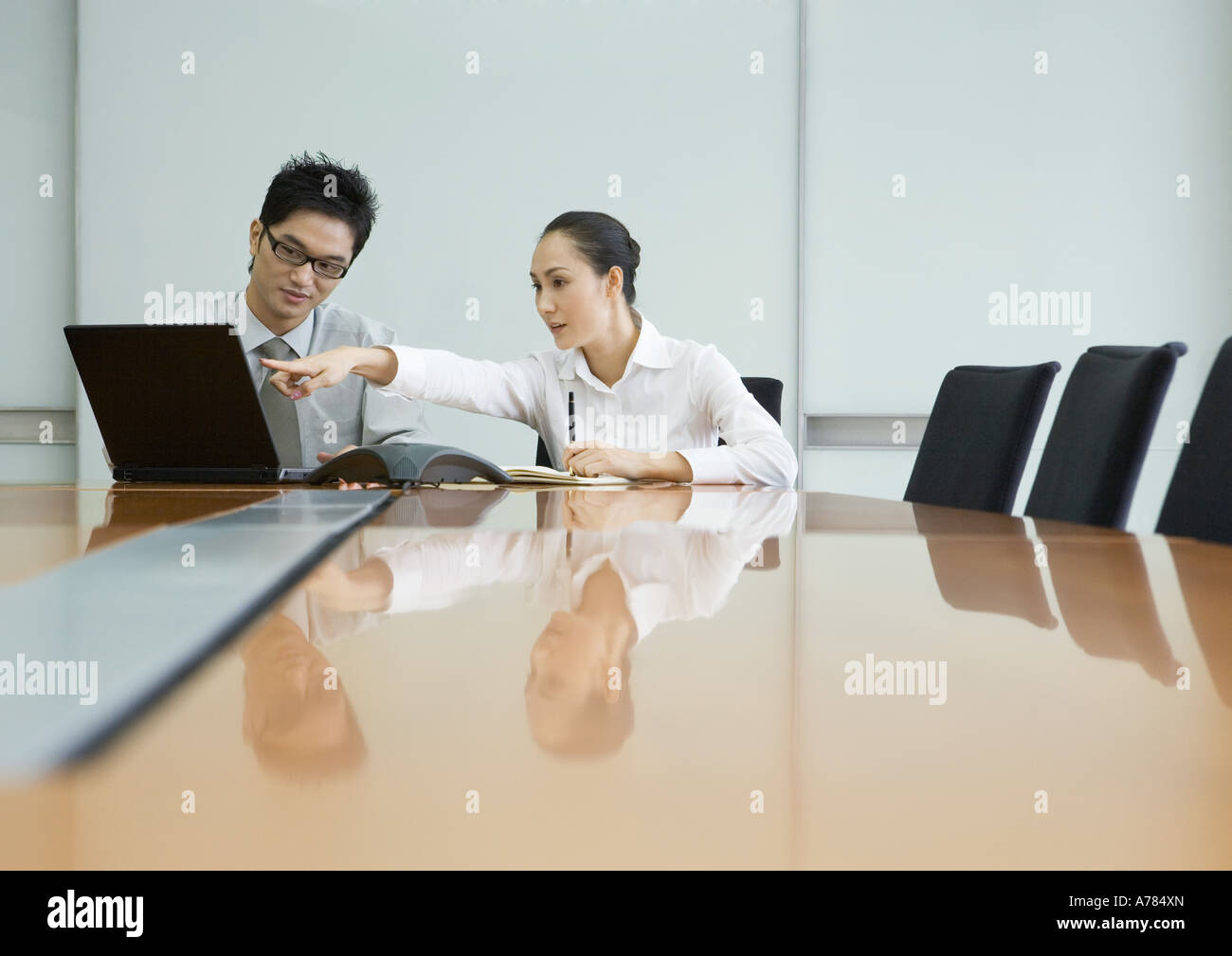 Two business executives working with laptop in conference room - Stock Image
