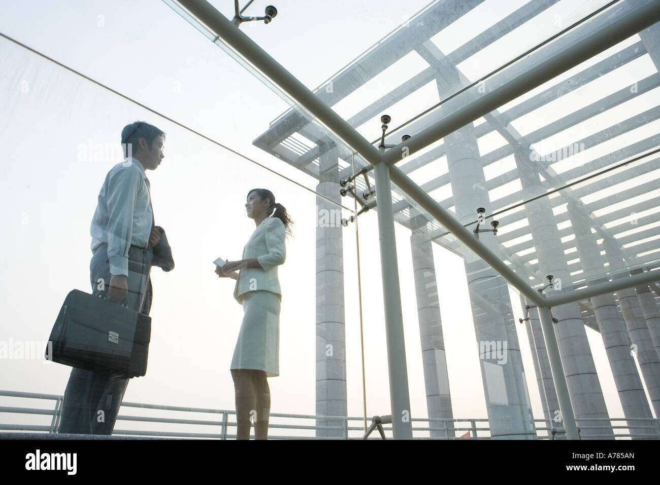 Young business executives standing under covered walkway, face to face, low angle view - Stock Image