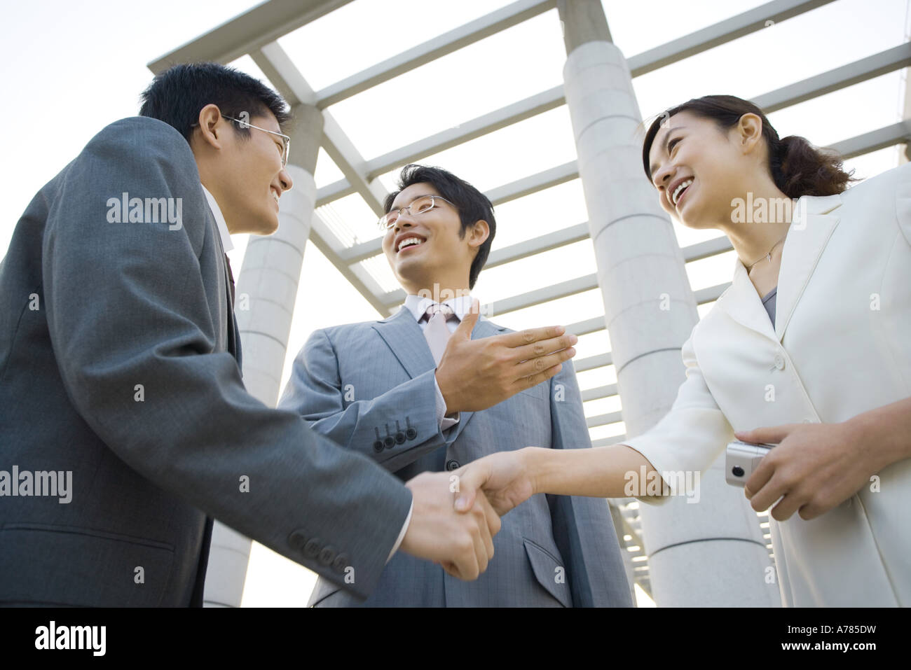 Business executives being introduced, low angle view - Stock Image