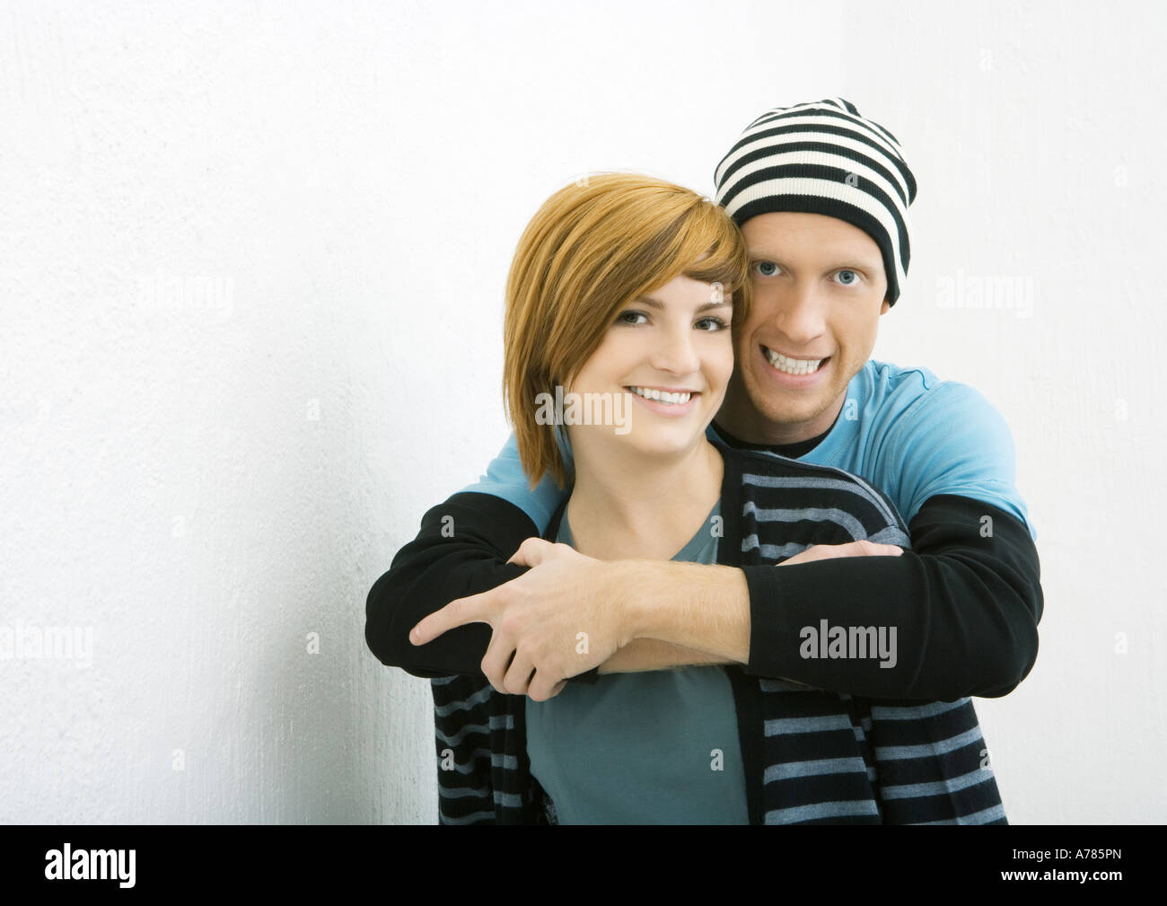 Young couple, man standing behind woman with arms around her, both smiling at camera - Stock Image