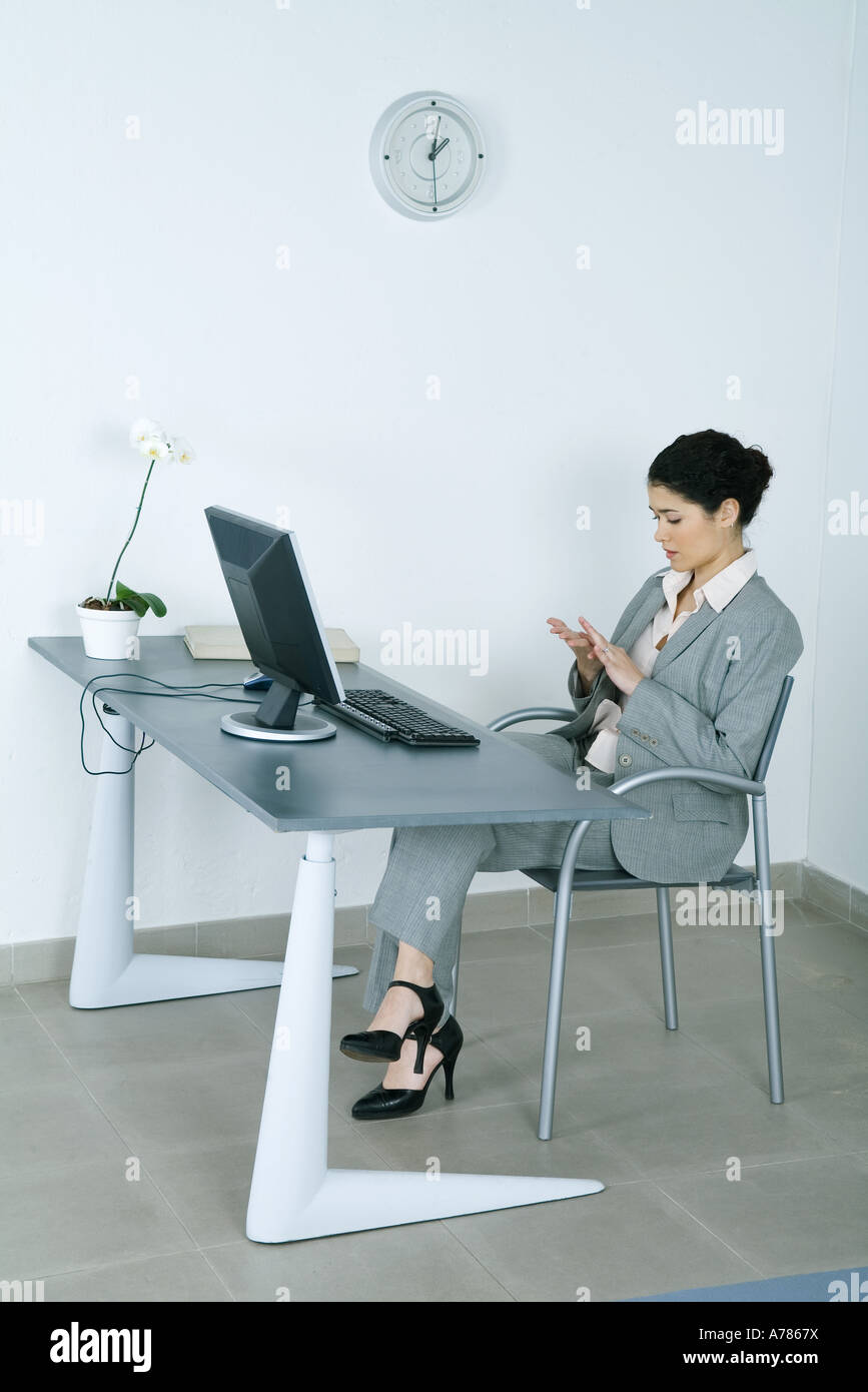 Businesswoman sitting at desk, looking at hands - Stock Image