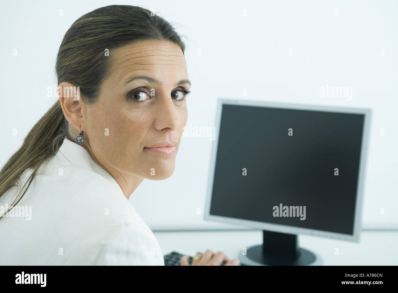 Businesswoman sitting at computer, looking over shoulder at camera - Stock Image