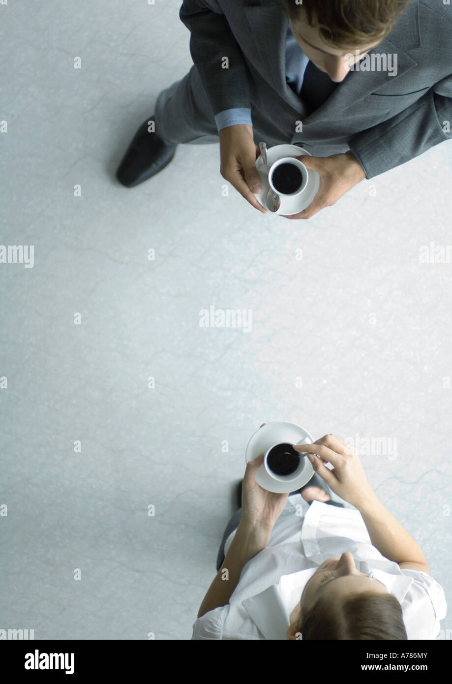 Office employees standing with coffee cups, view from directly above - Stock Image