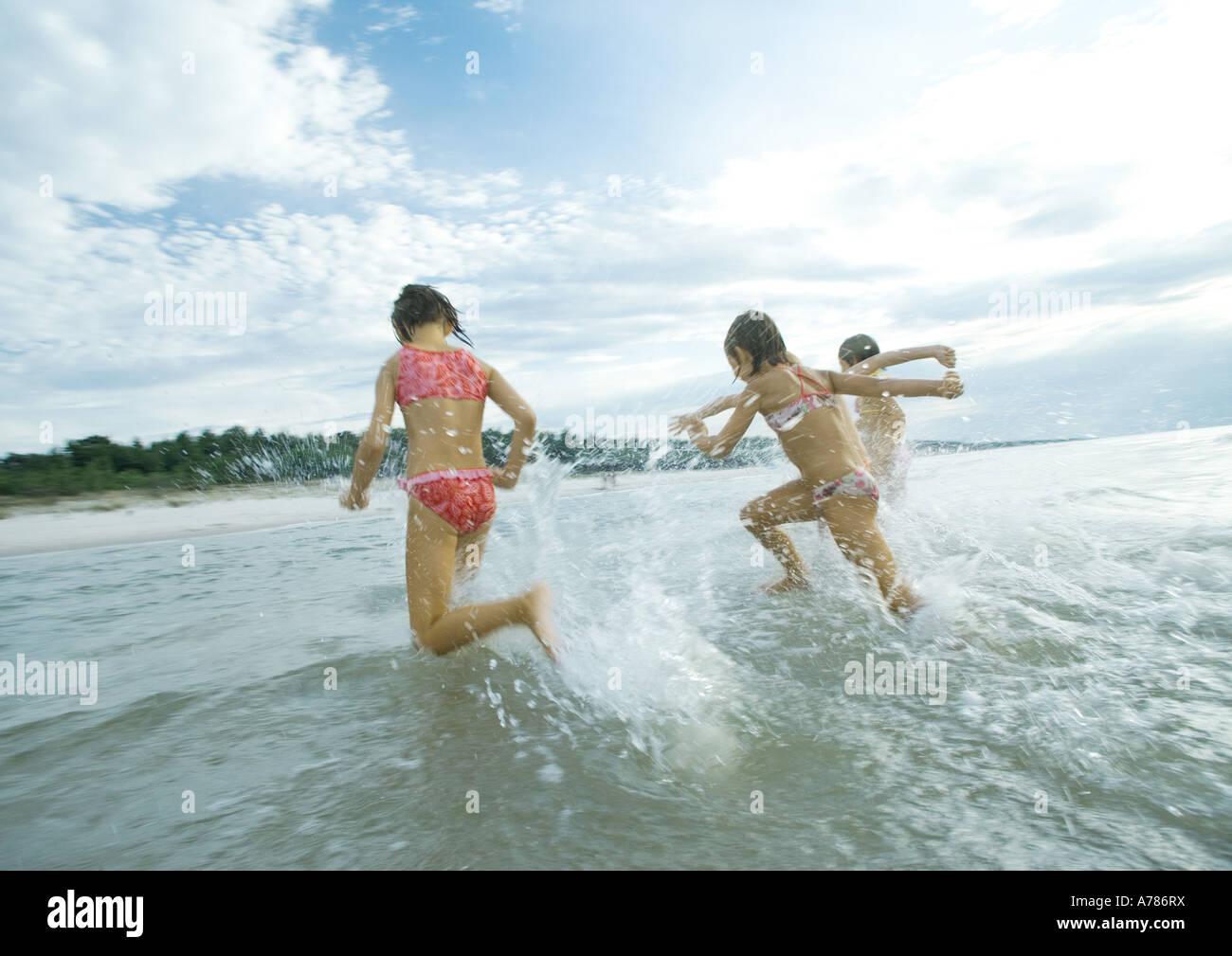 Children running in surf, rear view Stock Photo