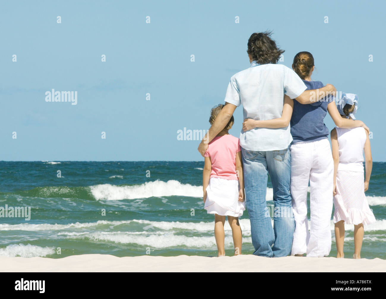Family standing next to surf, facing ocean, rear view - Stock Image