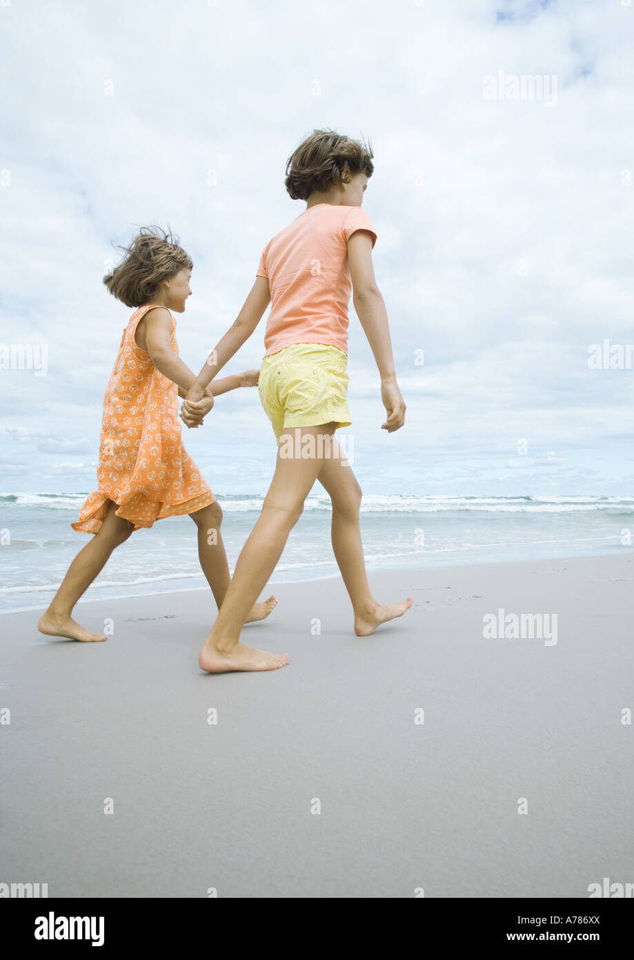 Two girls walking, holding hands, on beach - Stock Image