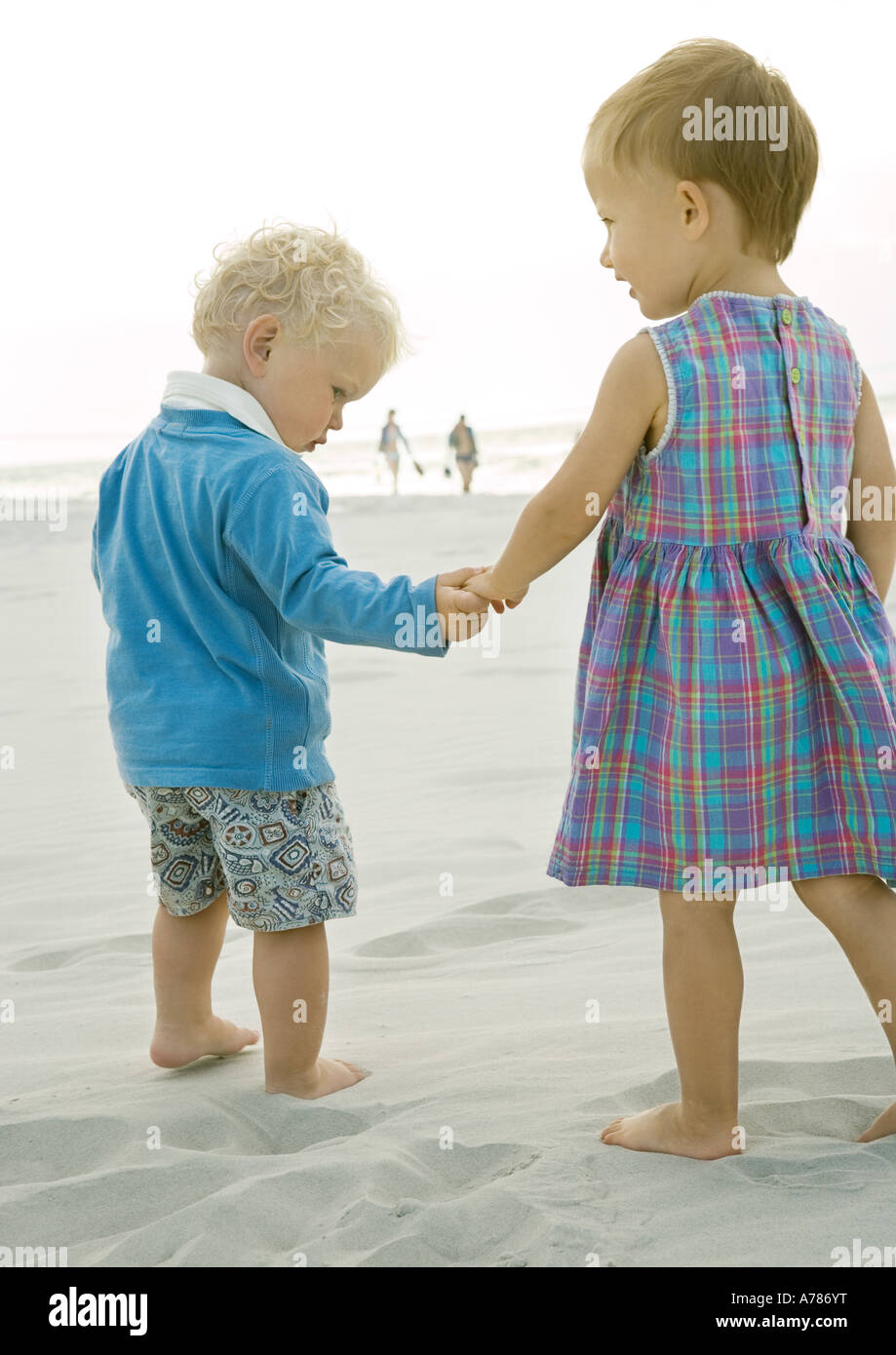 Two toddlers standing on beach, rear view - Stock Image