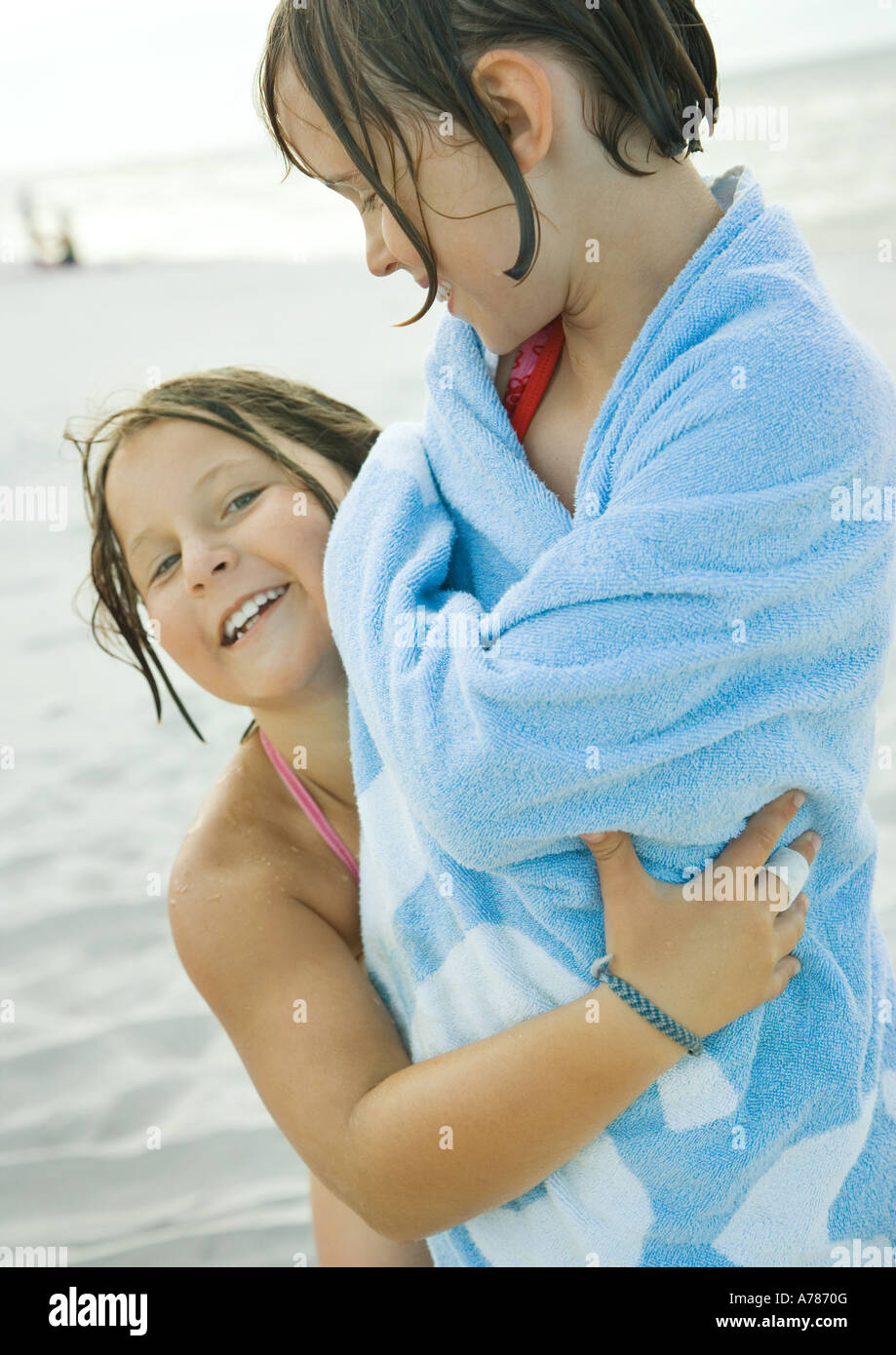 Two girls on beach, one wrapped in towel, the other holding girl around waist - Stock Image