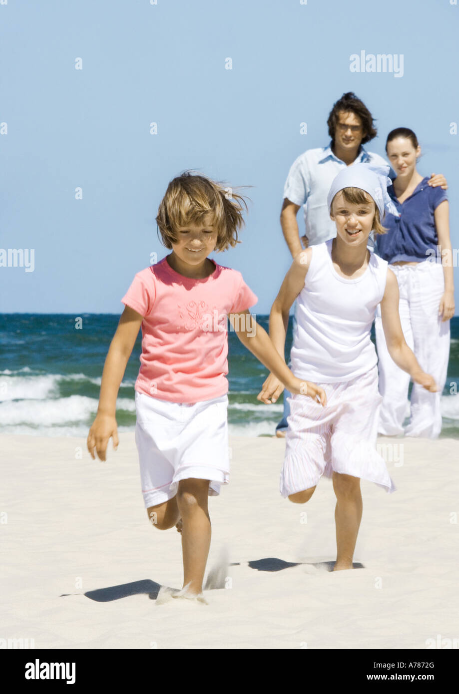 Girls running on beach while parents stand in background - Stock Image