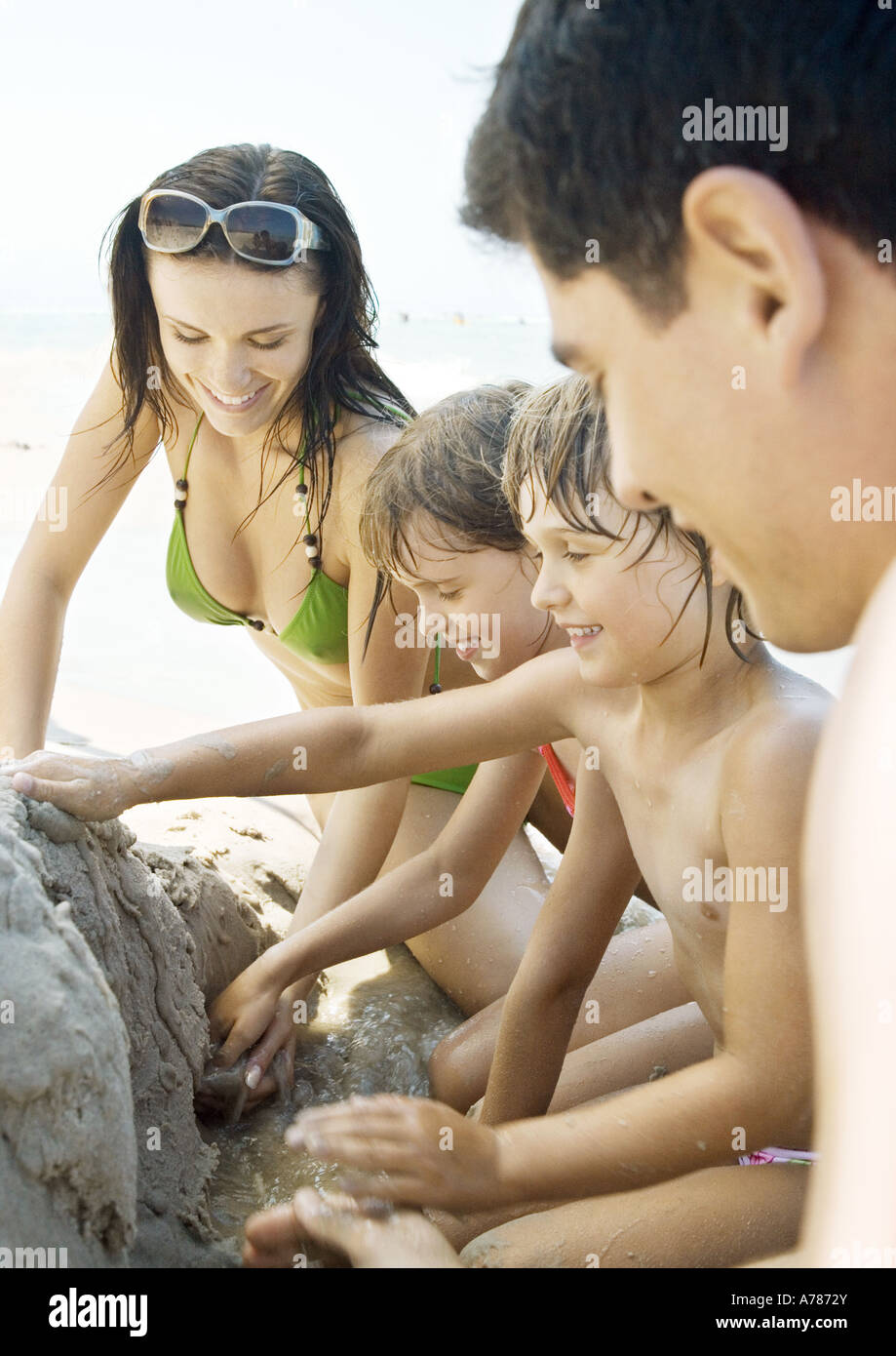 Family playing in sand on beach together Stock Photo