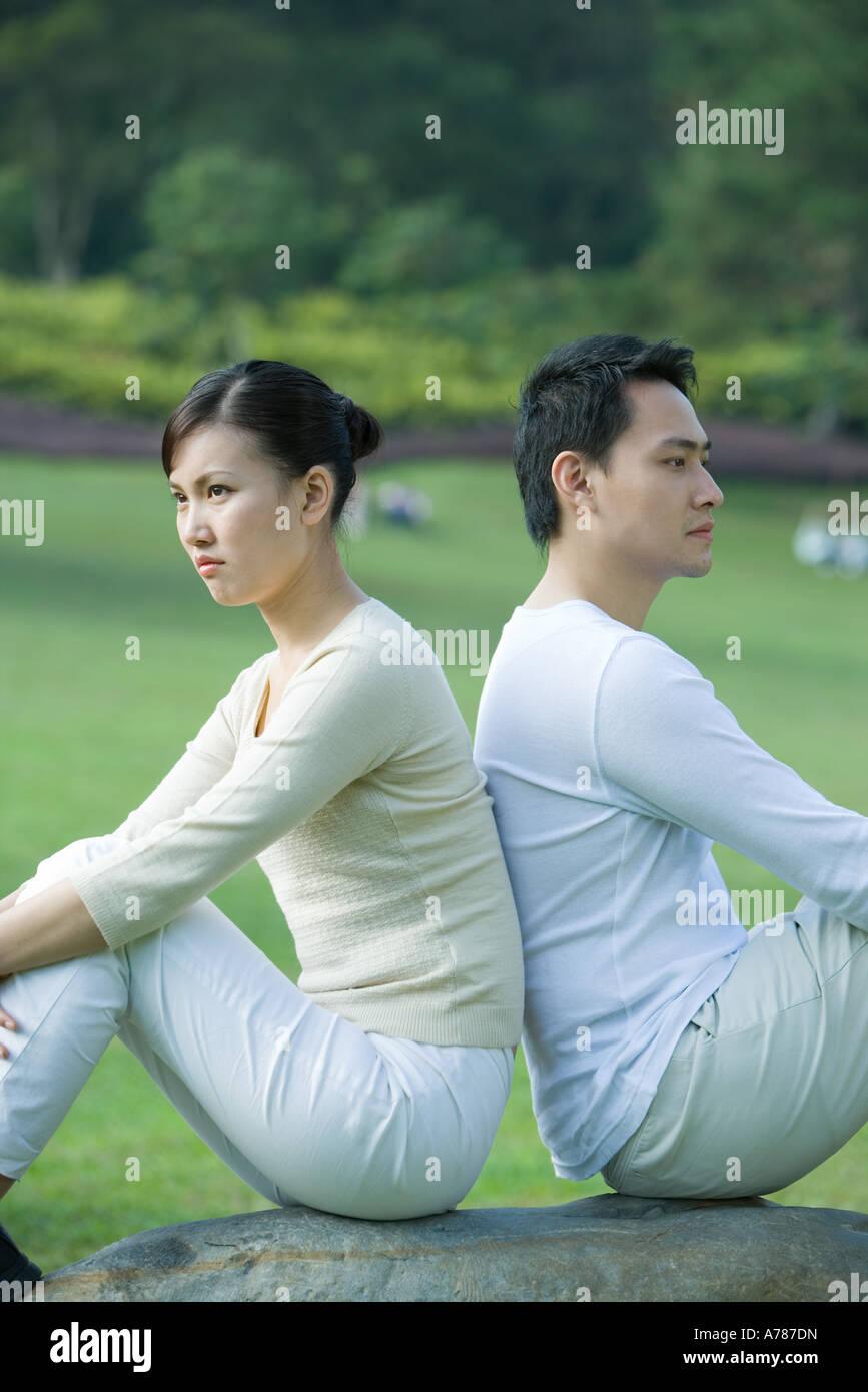Couple sitting back to back - Stock Image