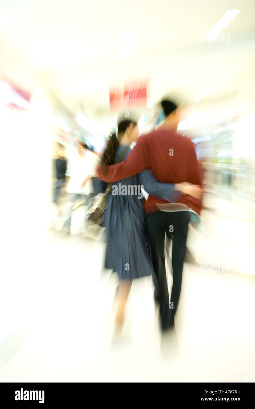 Couple walking through shopping mall, rear view, full length, blurred motion Stock Photo