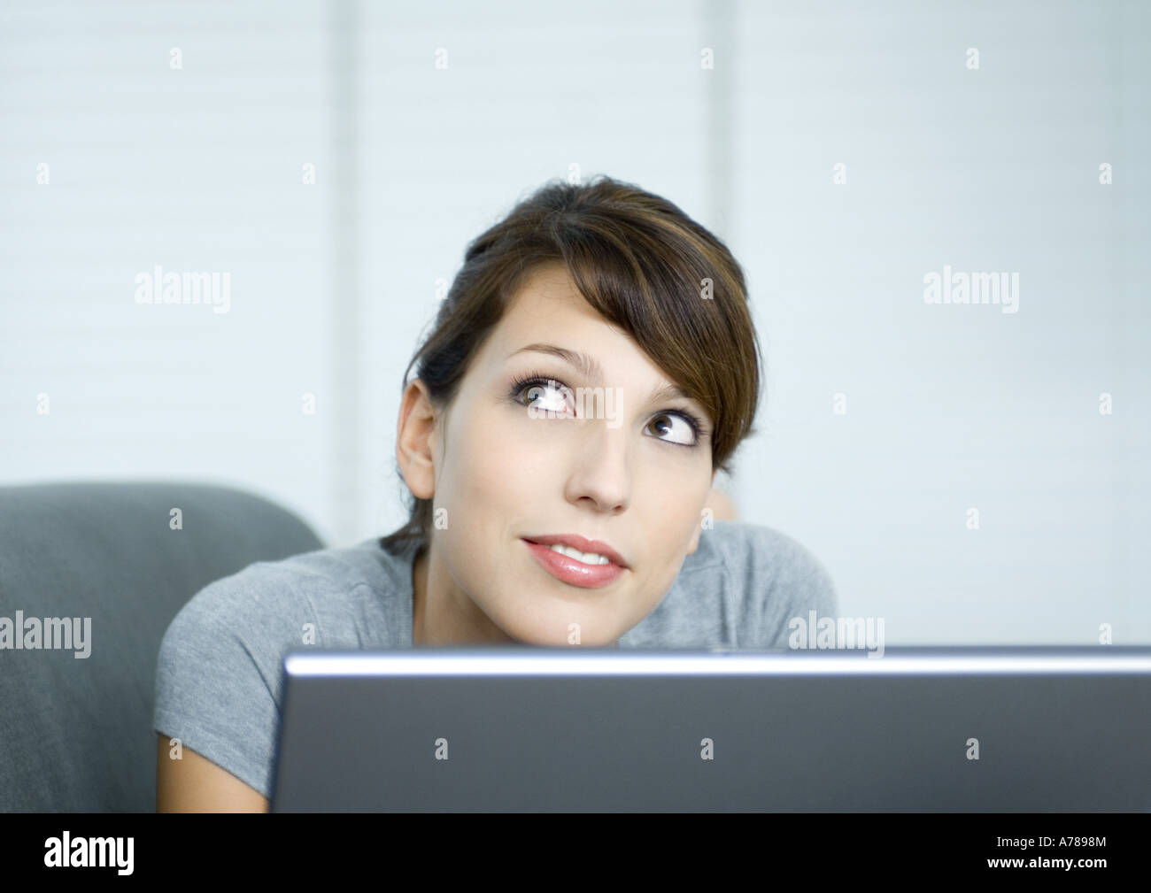 Young woman on couch, using laptop - Stock Image